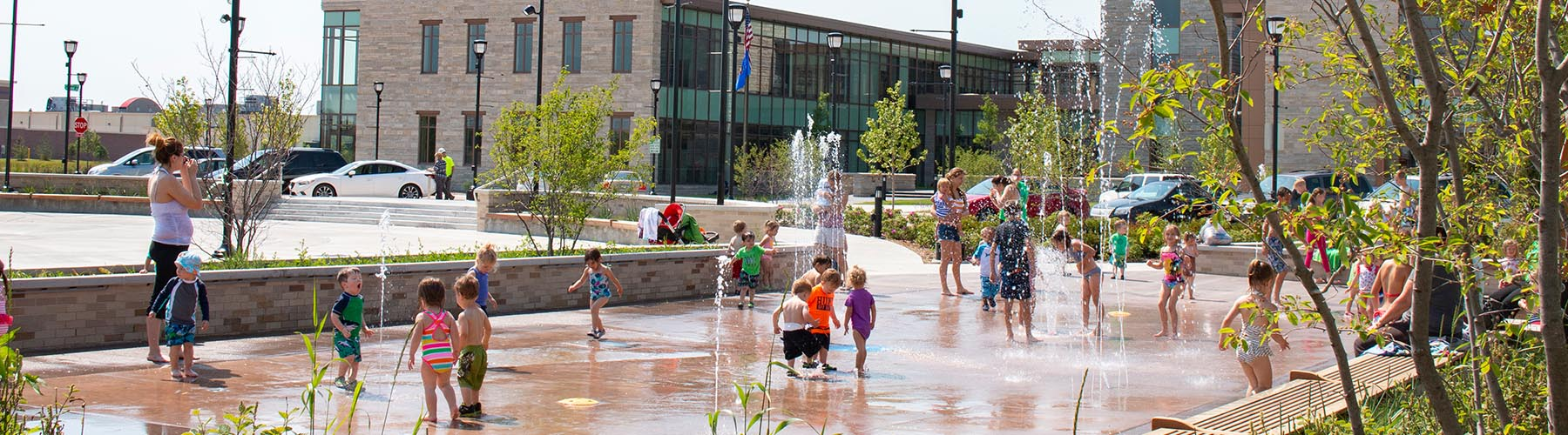 Kids playing on Splash Pad in front of Civic Center