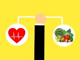 Cartoon hand holding a cartoon heart and healthy food made to look like a balanced scale